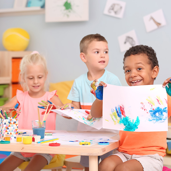 Cute children painting with their palms at table indoor